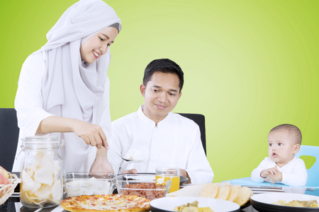Young wife preparing food for family in dining table while her husband and child sitting with green background