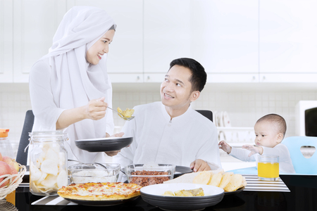 自宅に自分の赤ちゃんを浮かべている間彼女の夫に食事を与える若いイスラム教徒の女性の肖像画 写真素材 - 78226536