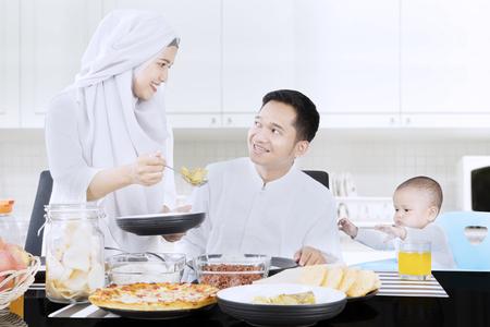 Portret van een jonge moslimvrouw die maaltijd geeft aan haar echtgenoot terwijl thuis het glimlachen met hun baby
