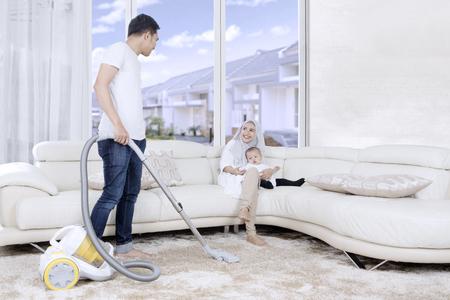 Jonge man reinigen tapijt met stofzuiger terwijl zijn vrouw en kind op de bank zitten