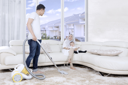 chores: Young man cleaning carpet with vacuum cleaner while his wife and child sitting on the couch