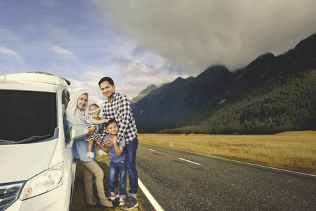 familia viaje: Image of Muslim family resting and standing near their car while travelling in the mountain Foto de archivo