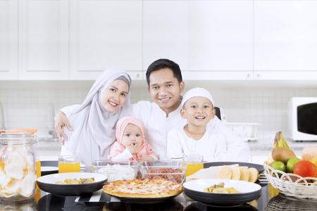 幸せな家族の笑顔一緒にキッチンでダイニング テーブルの前に座っている間の肖像画 写真素材
