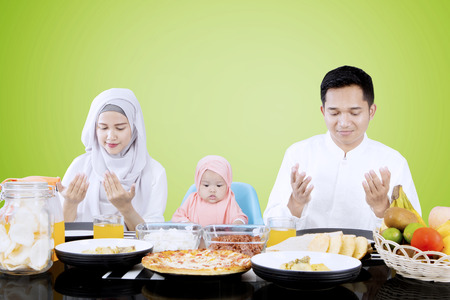 familia orando: Portrait muslim family praying before they eating while sitting in front of dining table with green background