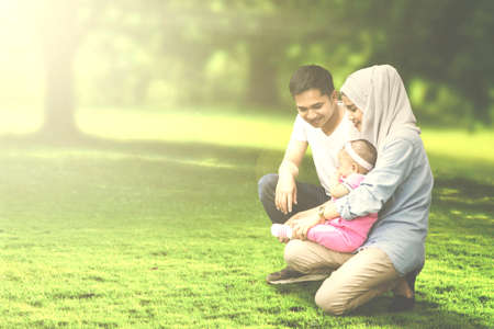 petite fille musulmane: Muslim parents playing with their baby girl while squatting in the meadow