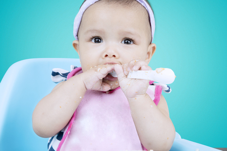 nip: Portrait of a female infant learn to eat and bites a porridge spoon with dirty hands on high chair, shot with blue screen background