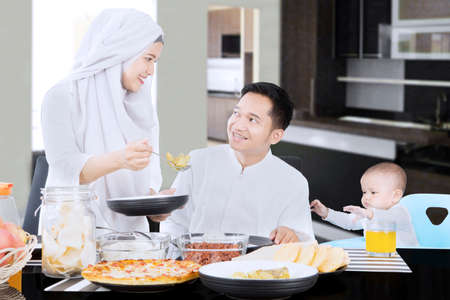 muslim baby girl: Happy Asian muslim family eating together on the table at home with a little baby