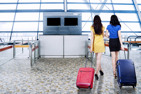 Back view of two women walking in the airport terminal while carrying suitcases for holiday