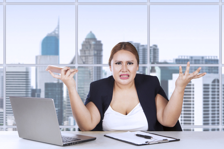 shrugs: Portrait of young entrepreneur confused with her job while shrugs her shoulder in the office Stock Photo