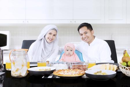 식탁 앞에 앉아있는 동안 작은 딸과 무슬림 부모가 부엌에서 웃고있다. 스톡 콘텐츠