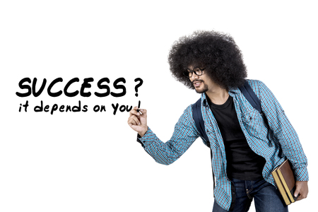 depends: Young afro man writing success it depends on you word on whiteboard while holding book, isolated on white background Stock Photo