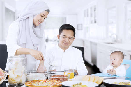 Young woman preparing food for family in dining table while her husband and child sitting in the kitchen