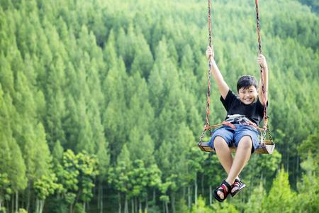 Het beeld van de kleine jongen ziet er gelukkig uit terwijl hij op een schommel met een mooi dennenbos speelt