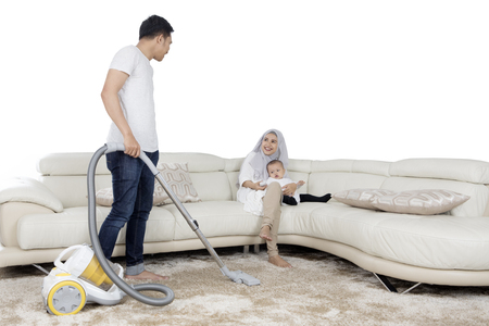 petite fille musulmane: Young husband cleaning floor mat with vacuum cleaner while his wife smiling on the sofa, isolated on white background Banque d'images
