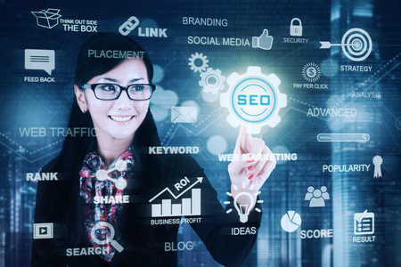 Young Asian businesswoman pressing SEO icon on a virtual screen. Concept of Search Engine Optimization photo