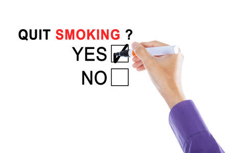 answer: Picture of businessmans hand choosing a yes option with a marker for quit smoking on the whiteboard
