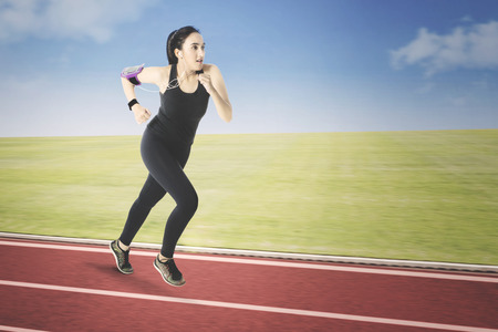 Pretty Arabian girl running on a running track while listening music with earphone and wearing smartwatch on her hand Stock Photo