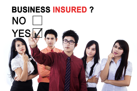 Image of business team selecting a yes option with text of business insured on the whiteboard photo