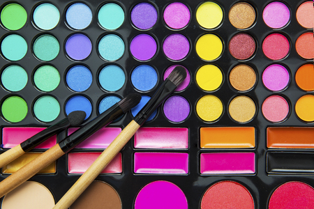 Close up of cosmetics brushes and luxury eyeshadow palette