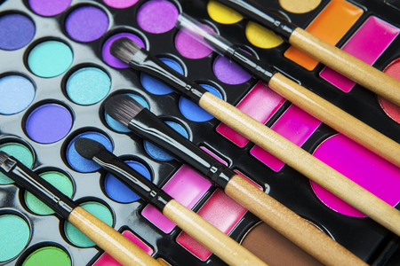 Close up of eyeshadow palette with make up brushes