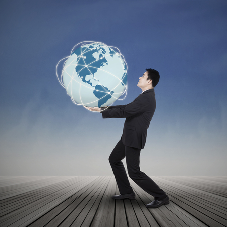 Young businessman lifting the earth planet outdoor photo