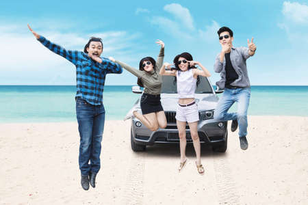 Multiracial group of young people wearing sunglasses, jumping together on the beach Stock Photo