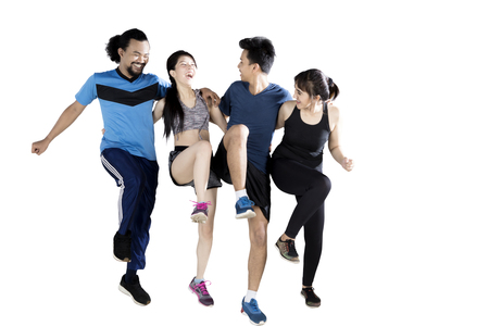 Multiracial group of friends exercising while laughing together, isolated on white background