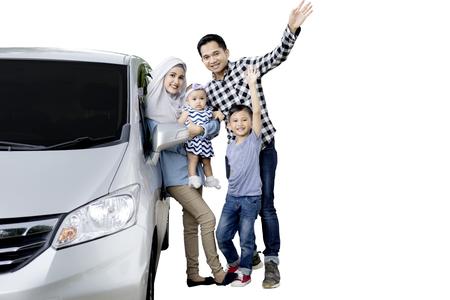 흰색 배경에 고립 된 그녀의 가족과 함께 서있는 동안 차에 기울고 아름 다운 어머니의 이미지