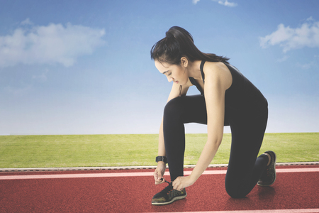 Pretty Arabian girl tying shoe laces on running track while wearing sportswear and smartwatch
