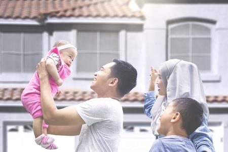 그들의 새 집 밖에 서 아기와 아들과 놀고 두 회교도 부모 스톡 콘텐츠
