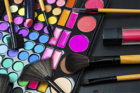 Close up of professional make up with colorful eyeshadow palette on dark background