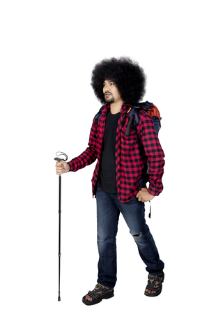 Afro man ready for hiking while wearing casual clothes with backpack and trekking pole, isolated on white background Stock Photo
