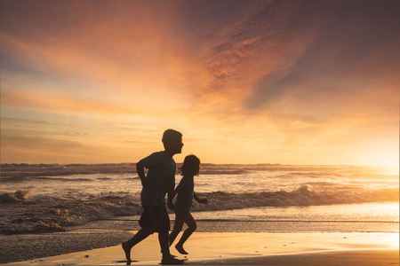 freedom: Little girl and boy running on the beach while holding hands at sunset time