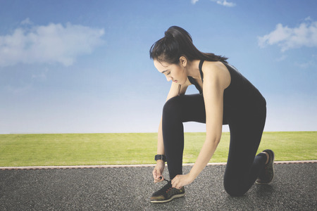 Portrait of beautiful female runner tying shoe laces on running trail using smartwatch heart rate monitor. Stock Photo