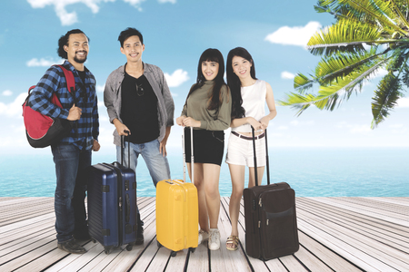 Multiracial of young people standing on seaside together while holding suitcase Stock Photo