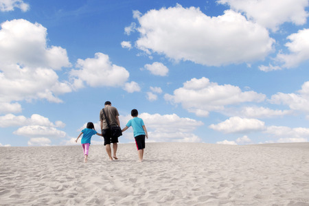 Rear view of happy family walking on the sand dune under the clouds on blue sky Stock Photo