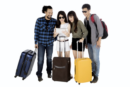 Group of young people looking at digital tablet together while holding suitcase, isolated on white background