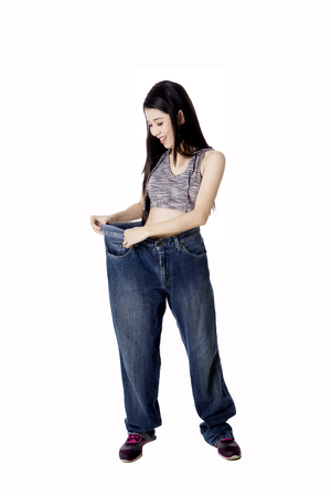 huge: Diet concept. Young happy woman wearing her old jeans after success doing weight loss, isolated on white background Stock Photo