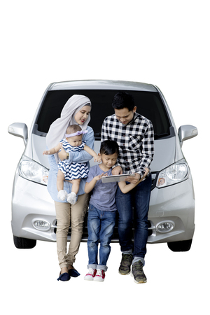 Portrait of Muslim family using a digital tablet while sitting on the hood of their car, isolated on white background Stock Photo