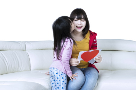 Photo of a female kid kissing her mom on the sofa after giving a greeting card with love symbol, isolated on white background photo