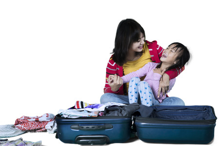 Picture of Asian mother preparing their clothes for vacation while laughing with her daughter, isolated on white background photo