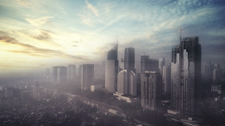 Aerial view of Jakarta city with skyscrapers on misty morning at sunrise time