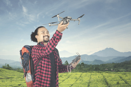 Young Afro man holding a drone and ready to play with a remote control at tea plantation