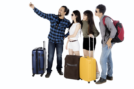 Multi ethnic group of friends taking selfie picture with smartphone while standing together, isolated on white background