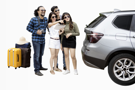 Multi ethnic group of happy friends looking something while standing behind the car, isolated on white background
