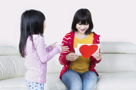 Photo of a young happy mother sitting on the couch while reading a greeting card from her daughter with love symbol photo