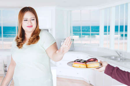 offered: Portrait of fat woman refused donuts offered her friend while standing at home