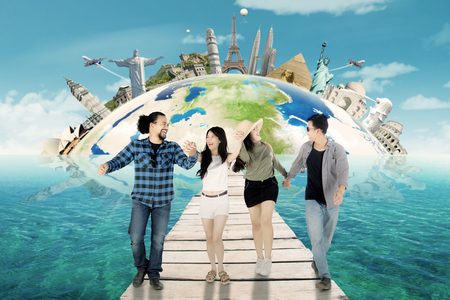 Multiracial of cheerful young people walking on the wooden bridge with famous landmark on globe