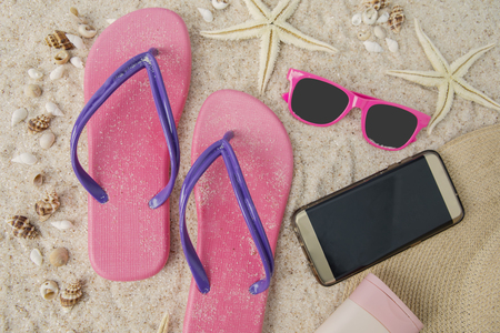 e94ecce68 Close up of smartphone and beach item on the sandy beach with seashells  Stock Photo
