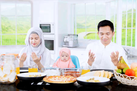 family together: Happy family praying before they eating while sitting in front of dining table in the kitchen Stock Photo
